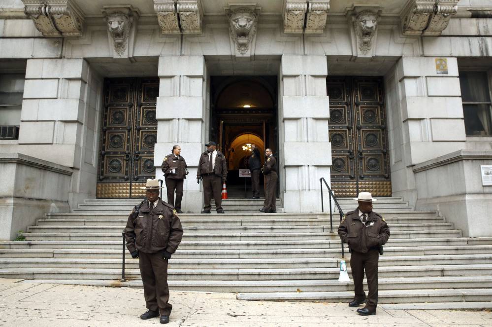 Members of the Baltimore City Sheriff's Office stand outside Clarence M. Mitchell Jr. Courthouse, Monday in Baltimore, after the arrival of William Porter, one of six Baltimore city police officers charged in connection to the death of Freddie Gray.