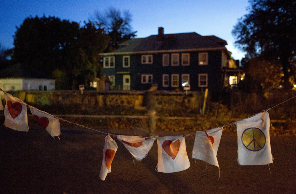 A string of flags with hearts and peace signs serves as a memorial as emotions still run strong a year after a fire on Portland's Noyes Street killed six people in their 20s.
