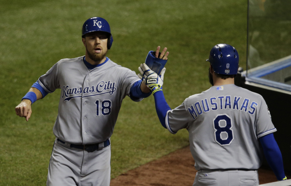 Kansas City's Ben Zobrist is congratulated by Mike Moustakas after scoring on a single by Lorenzo Cain in the sixth inning. Zobrist also scored the tying run in the eighth, and Moustakas drove in the go-ahead run.