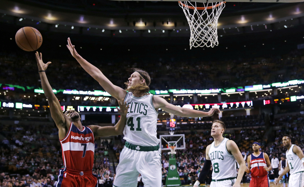 Celtics center Kelly Olynyk blocks a shot by Wizards guard Ramon Sessions in the first quarter of Boston's lopsided win Friday night. The Celtics outscored Washington 40-25 in the first quarter.