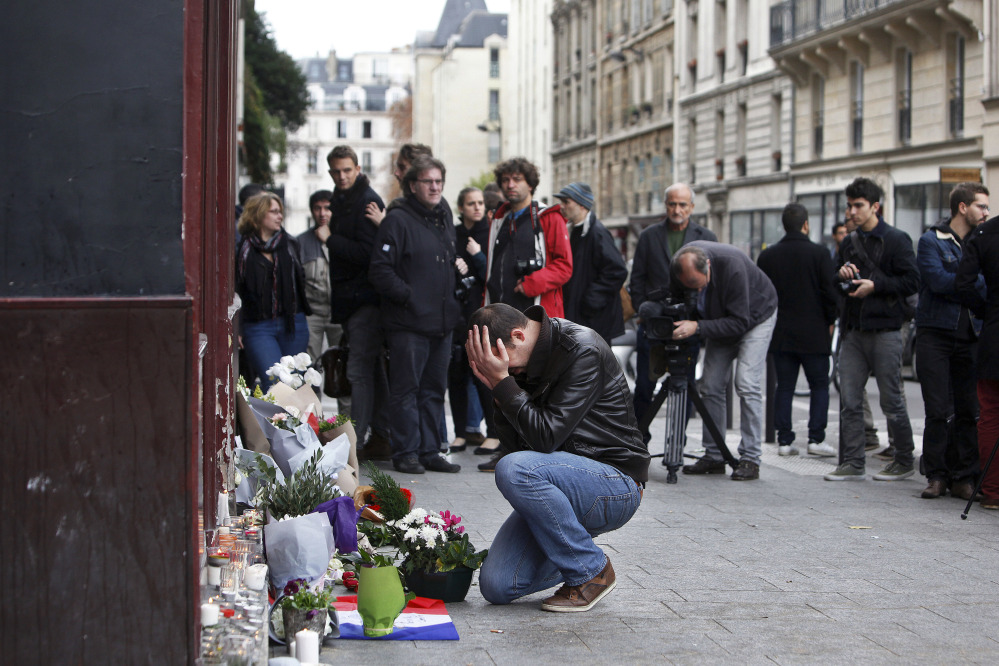 A man holds his head in his hands as he lays flowers in front of the Carillon cafe, in Paris on Saturday. French President Francois Hollande vowed to attack Islamic State without mercy as the jihadist group admitted responsibility Saturday for orchestrating the deadliest attacks inflicted on France since World War II.