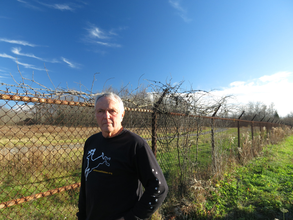 Dennis Money, president of Seneca White Deer Inc., stands beside the perimeter fence of the former Seneca Army Depot in Romulus, N.Y.. The weapons storage site is up for sale and Money hopes to buy all or part of the land in partnership with The Nature Conservancy to save the hundreds of rare white deer there. The Associated Press