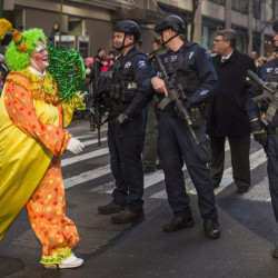 "A clown marches past heavily armed police officers during the Thanksgiving Day parade in New York. ""It's a little scary, but at least it's keeping us safe,"" said Kim Miller of Boston."