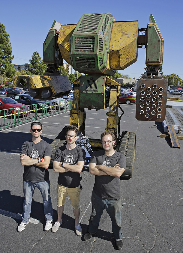 MegaBots founders from left, Brinkley Warren, Matt Oehrlein and Gui Cavalcanti stand below their 15-foot tall, piloted Mk.II robot at the Pioneer Summit in Redwood City, Calif., recently. The Associated Press