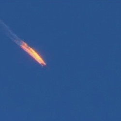 This frame grab from video by Haberturk TV, shows a Russian warplane on fire before crashing on a hill as seen from Hatay province, Turkey, on Tuesday. The Associated Press