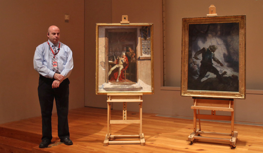 """Portland Museum of Art security officer Shawn Higgins stands next to the two N.C. Wyeth paintings – """"""""Go Dutton, and that right speedily,"""" left, and """"The Encounter on Freshwater Cliff"""" – recovered in early October. They were among six stolen from Portland landlord Joseph Soley in 2013.. Whitney Hayward / Staff Photographer"""