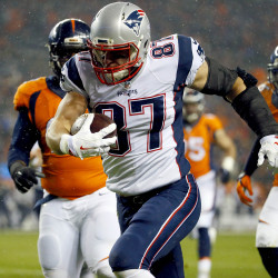 New England Patriots tight end Rob Gronkowski (87) scores a touchdown as Denver Broncos nose tackle Sylvester Williams (92) defends during the first half Sunday. The Associated Press