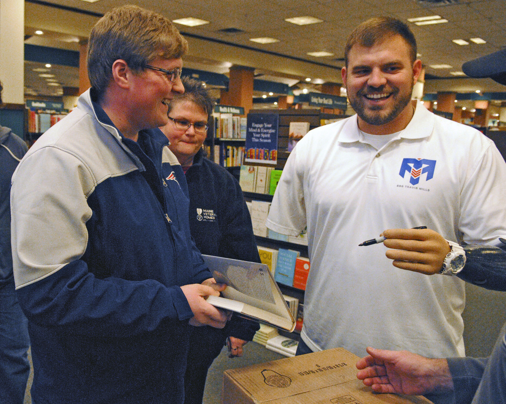 "Travis Mills, right, jokes around with customers while autographing a copy of his book ""Tough As They Come"" on Tuesday at the Barnes and Noble store in Augusta."