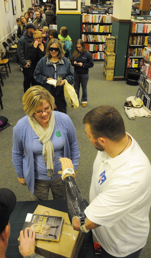 "Travis Mills, right, jokes with a customer while demonstrating the rotating wrist on his prosthetic arm Tuesday at a book signing where he autographed copies of his autobiography, ""Tough As They Come,"" at the Barnes & Noble bookstore in Augusta."