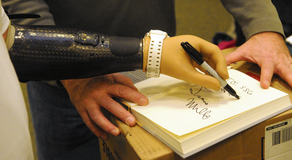 "Travis Mills autographs a copy of his book ""Tough As They Come"" with his left prosthetic hand on Tuesday at the Barnes and Noble store in Augusta. Mills made jokes with customers that used to be right handed but had to learn to write with left."