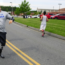 Travis Mills waves to other participants as he runs in the 4th annual Miles for Mills 5k on May 25 at Cony High School in Augusta. Proceeds from the event benefited the Travis Mills Foundation, a nonprofit organization formed to help wounded and injured veterans.
