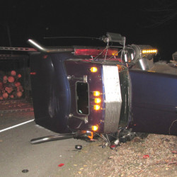 Maine State Police contributed photo A pulp truck that overturned after it was hit by a car on U.S. Route 2 in Mexico Monday night. The driver of the car lost control after hitting a dead dear in the road and veering into the path of the truck.