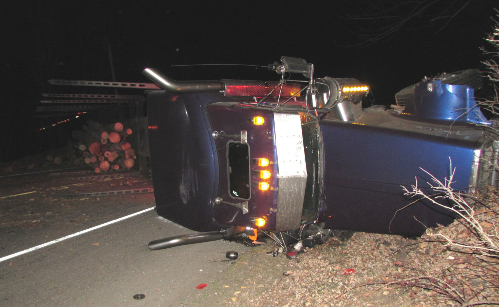 Maine State Police contributed photo A pulp truck that overturned after it was hit by a car on U.S. Route 2 in Mexico Monday night. The driver of the car lost control after hitting a dead deer in the road and veering into the path of the truck.