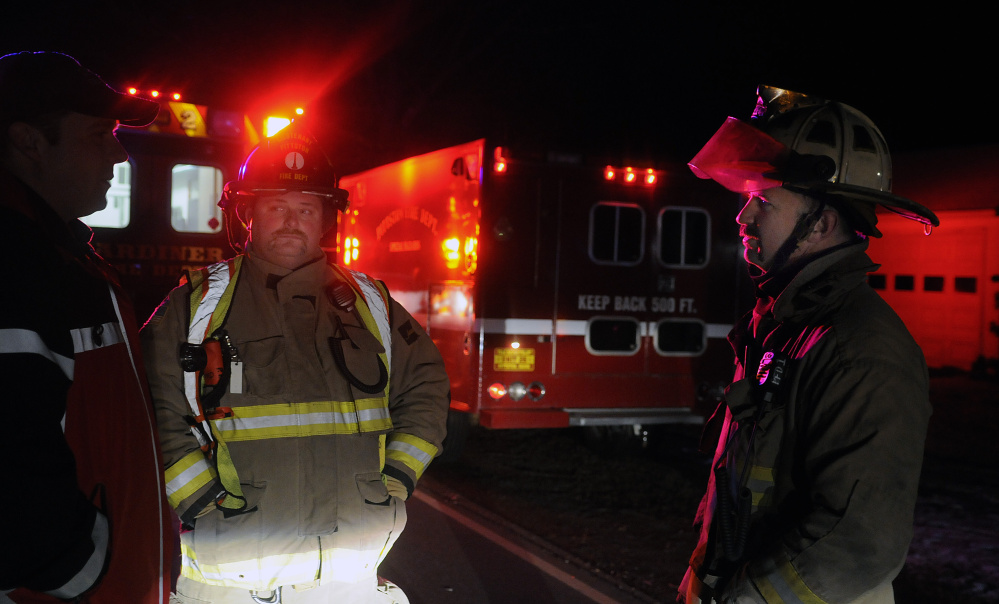 Pittston Fire Chief Jason Farris, right, and Lt. Mike Flanders, center, speak Monday with Gardiner Fire Dept. Captain Pat Saucier at a fatal accident on Route 194 in Pittston. An 83-year-old volunteer firefighter died while crossing the road to get to his mailbox.