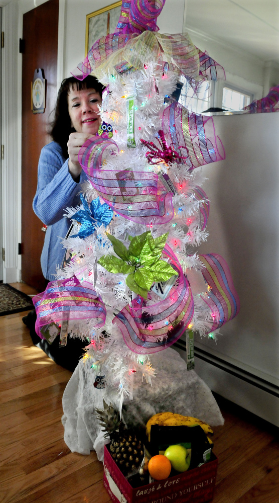 """Morning Sentinel columnist Amy Calder arranges gift cards on Tuesday on the Christmas tree she won at the Sukeforth Family Festival of Trees last month. She nicknamed the 4-foot-tall tree """"Little White."""""""