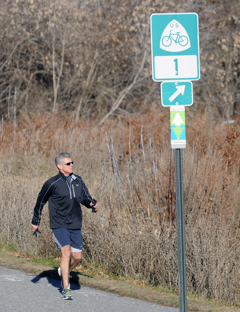 Jim Pietkiewicz, of Topsham, jogs Monday on the Kennebec River Rail Trail near Hallowell. Signs marking the East Coast Greenway bike trail have gone up in Augusta and Hallowell recently, as the trail continues to try to expand its reach.