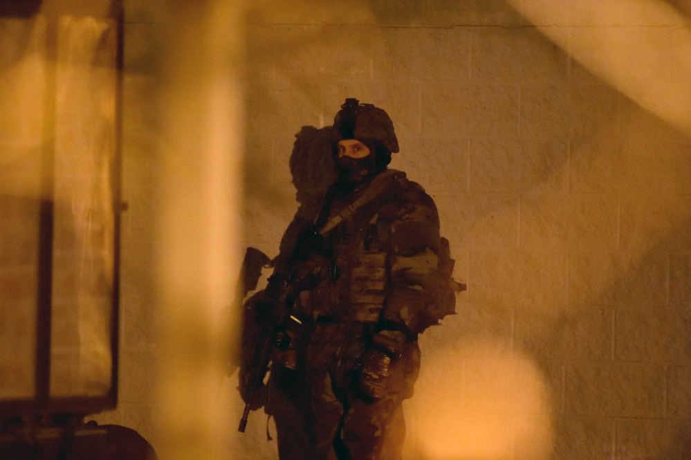 A member of the Maine State Police tactical team stands ready during a standoff with an armed man at the Waterville Police Department on Tuesday.