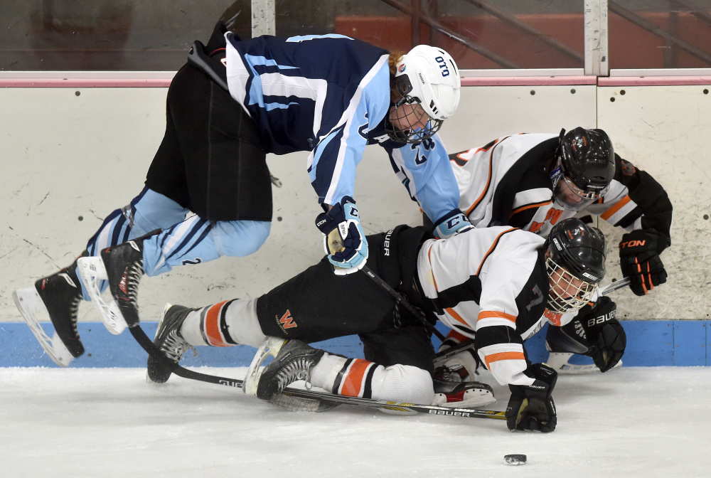Staff photo by Michael G. Seamans   Winslow forward Jimmy Fowler, bottom center, gets knocked over by Old Town/Orono's Chris Hoxie during a Class B North game Saturday night at Sukee Arena.