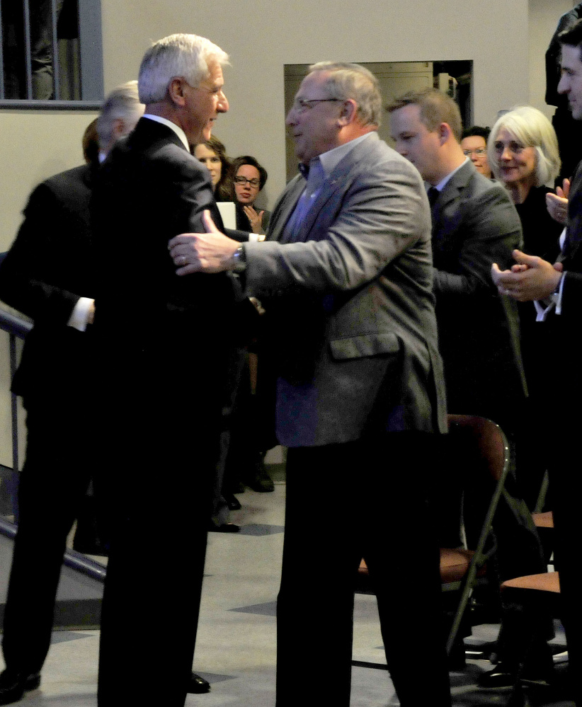Collaborative Consulting founder, president and CEO William C. Robichaud Sr., left, and Gov. Paul LePage shake hands after the announcement Wednesday that the company will open a business in the Hathaway Creative Center in Waterville.