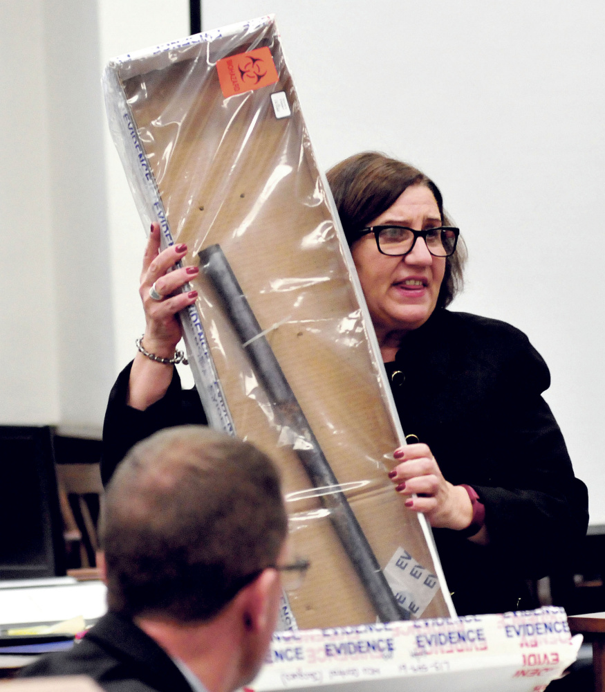 Assistant Attorney General Leanne Zainea holds a pipe as evidence that will be used in the murder trial of defendant Jason Cote accused of killing Ricky Cole during the first day of Cote's trial in Somerset County Superior Court in Skowhegan on Dec. 10.