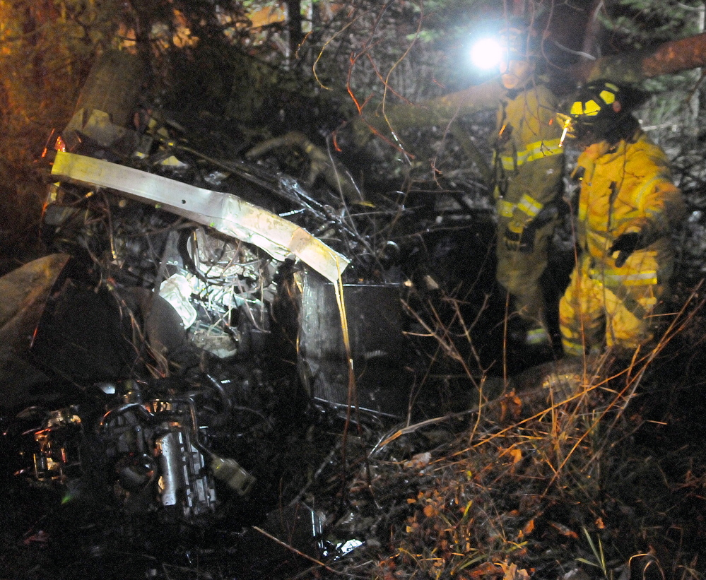Firefighters search the vehicle that Thorr Ellis was driving on Nov. 5, 2014 when it rolled over on Plains Road in Readfield, killing Alex Cruz, 26, of Connecticut.