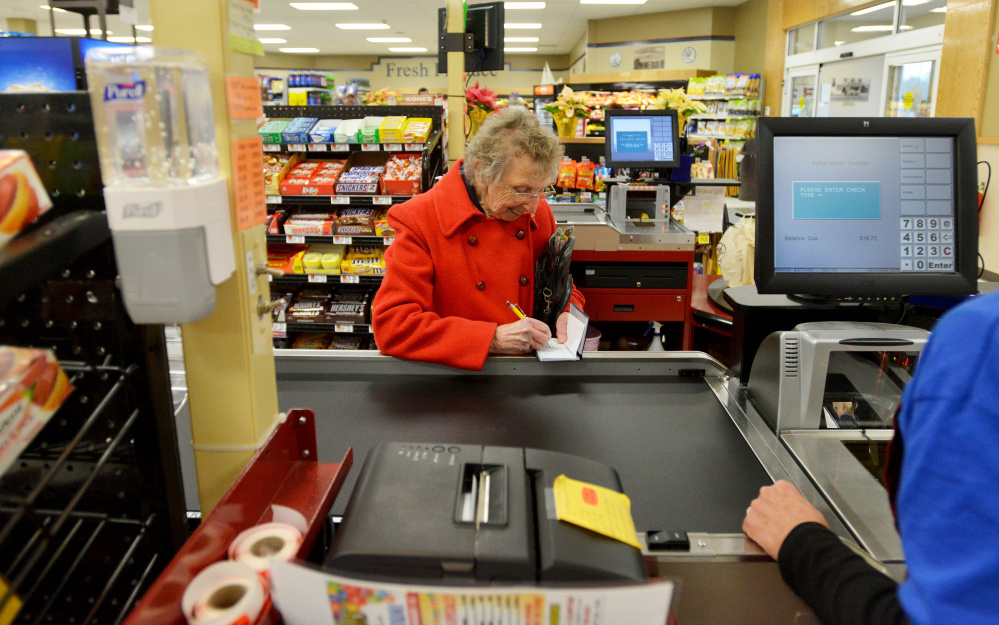 Marie Webb writes a check for her groceries as Kathy Selfridge rings her up during the grand opening of the Tradewinds Market on Hinckley Road in Clinton on Friday.