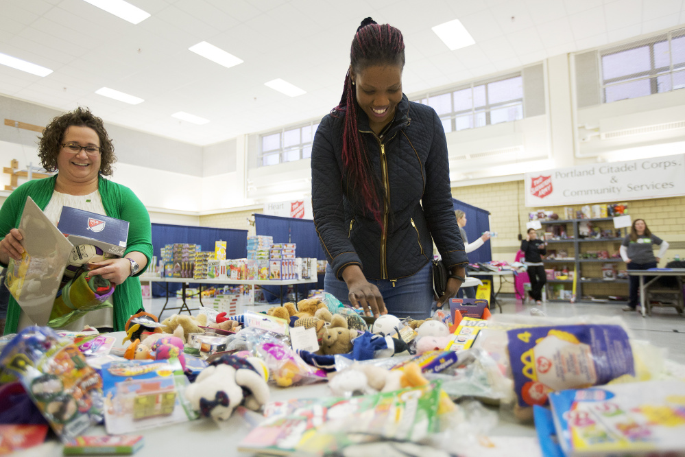 Viola Lupai looks through a table of stuffed animal toys Thursday at the Salvation Army's annual toy distribution program in Portland, which is funded by kettle donations, while volunteer Jessica Nason helps carry Lupai's toys.