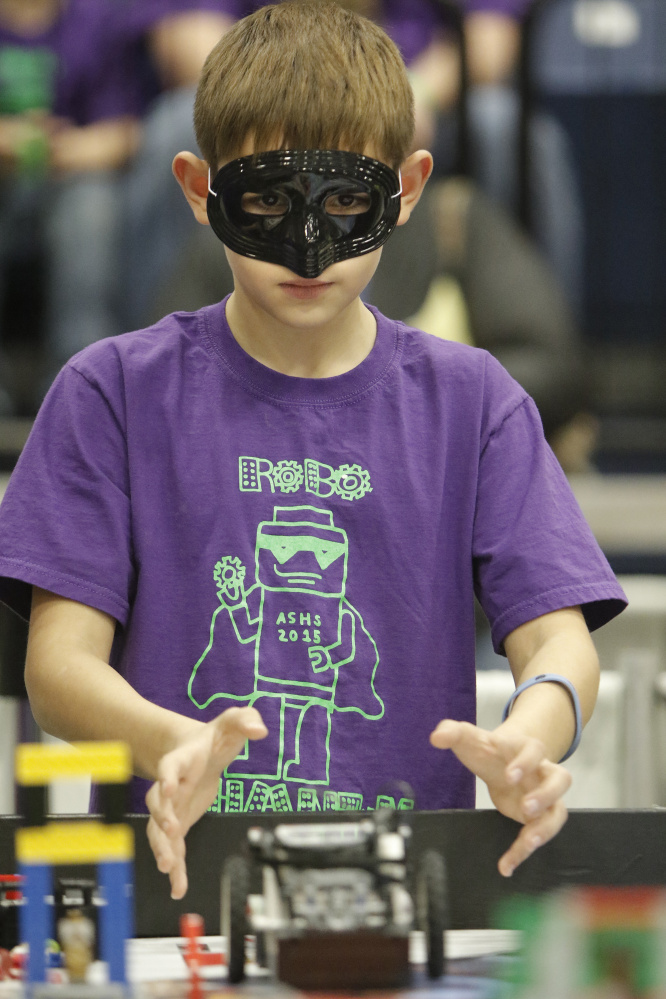 J.T. Trenholm, an fifth-grader at Albert S. Hall School in Waterville, lets go of his team's robot Saturday while competing in the Maine FIRST LEGO League State Championship at the Augusta Civic Center. Trenholm is wearing a mask as part of the costume of his team, named the Robo Phantoms. Sixty teams from around the state competed in the championship.