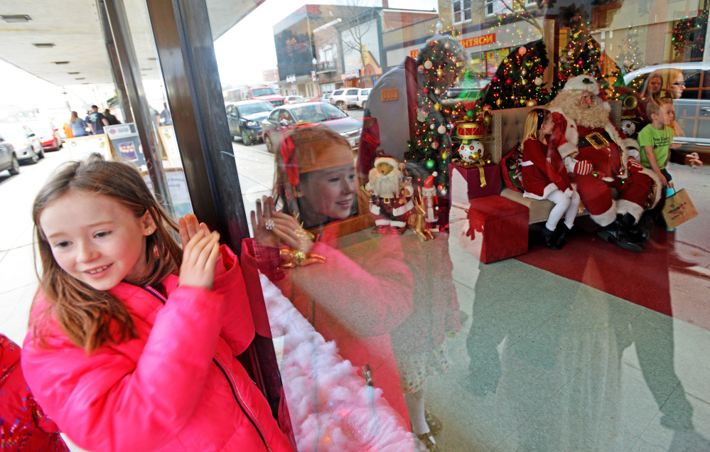 Liana Talty, 8, of Lincolnville, peeks through the window of the REM Center on Saturday to catch a glimpse of Santa Claus at Kringleville during the Downtown Waterville Open House.