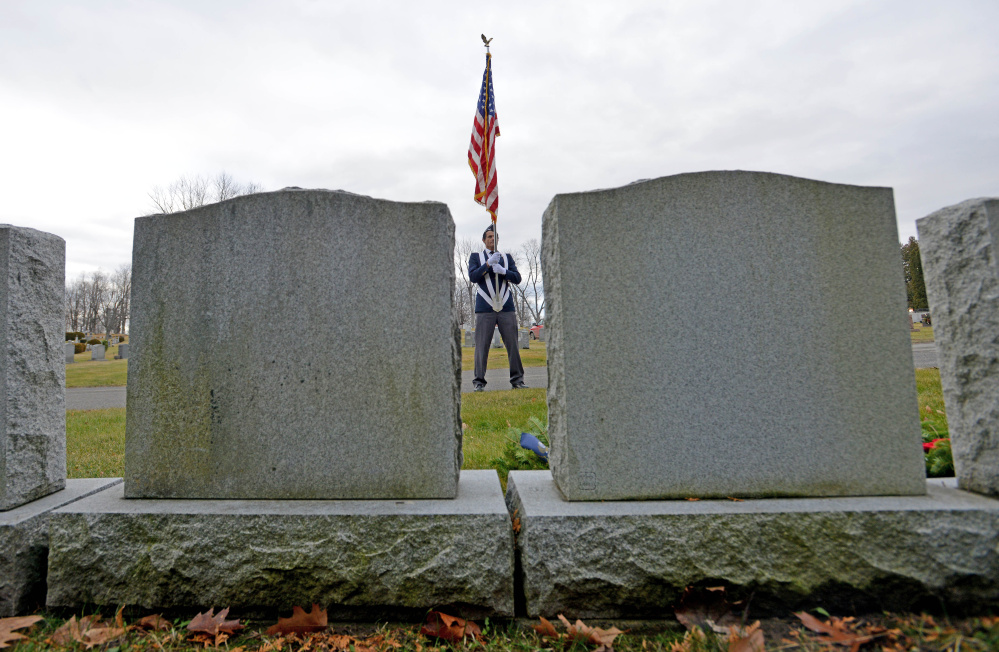 Bryant Bourgoin, a member of the men's auxillary of Waterville VFW Post 1285, stands at attention with the American flag during a wreath-laying ceremony Saturday at St. Francis Cemetery on Grove Street in Waterville. The wreaths, from Wreaths Across America, are being placed on veterans' graves across the nation.