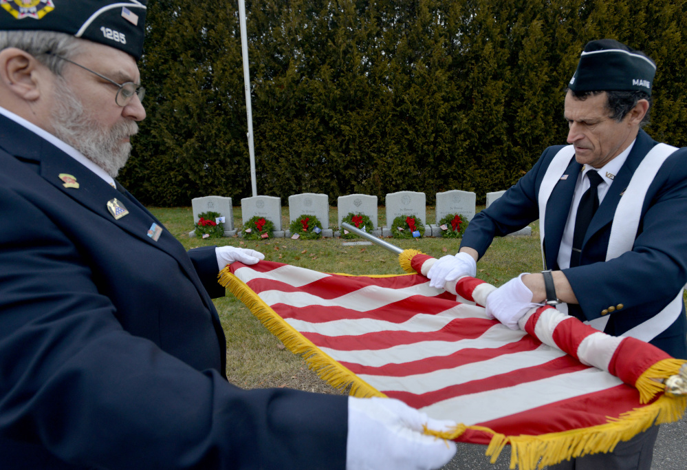 Waterville VFW post 1285 men's auxiliary members Forrest Breton, left, and Bryant Bourgoin roll the American flag Saturday after ceremoniously placing wreaths on military veterans' graves at St. Francis Cemetery on Grove Street in Waterville.