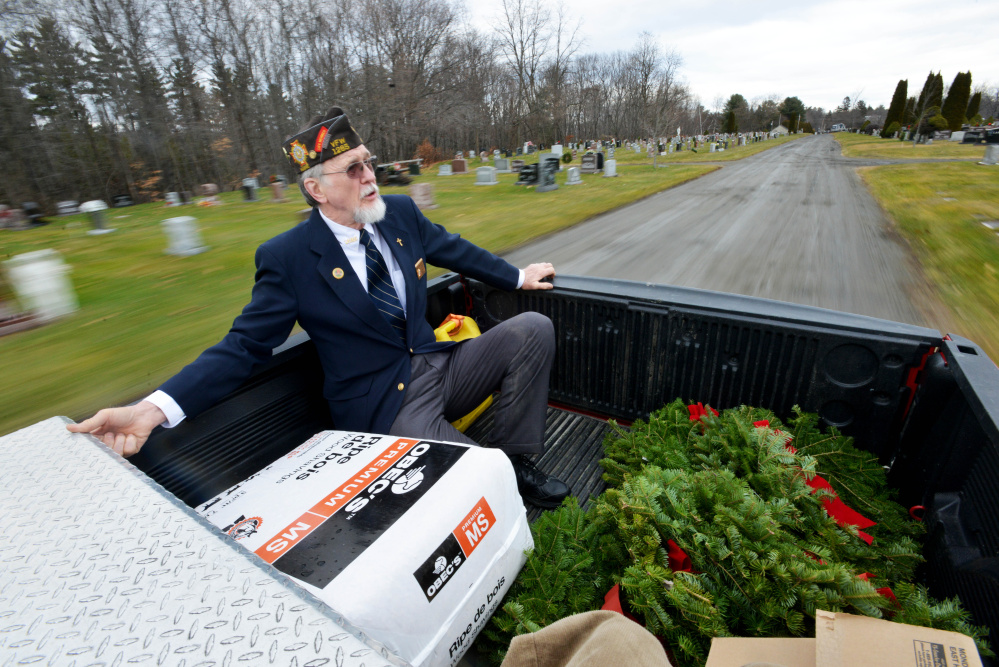 Waterville VFW Post 1285 member Charles McGillicuddy rides in the back of post Commander Daniel Parker's pickup truck Saturday as they work their way around St. Francis Cemetery on Grove Street in Waterville to deliver wreaths to veterans' graves.