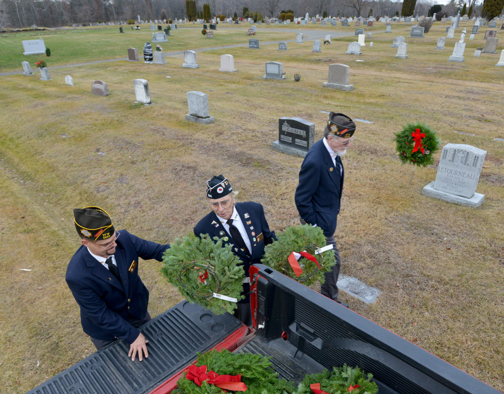 Waterville VFW Post 1285 Commander Daniel Parker, left, hands out wreaths Saturday to Paul Pontbriand, center, and Charles McGillicuddy, right, at St. Francis Cemetery on Grove Street in Waterville.