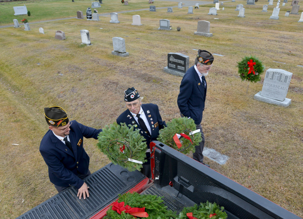 Waterville VFW Post 1285 Commander Daniel Parker, left, hands out wreaths on Saturday to Paul Pontbriand, center, and Charles McGillicuddy, right, at St. Francis Cemetery on Grove Street in Waterville.