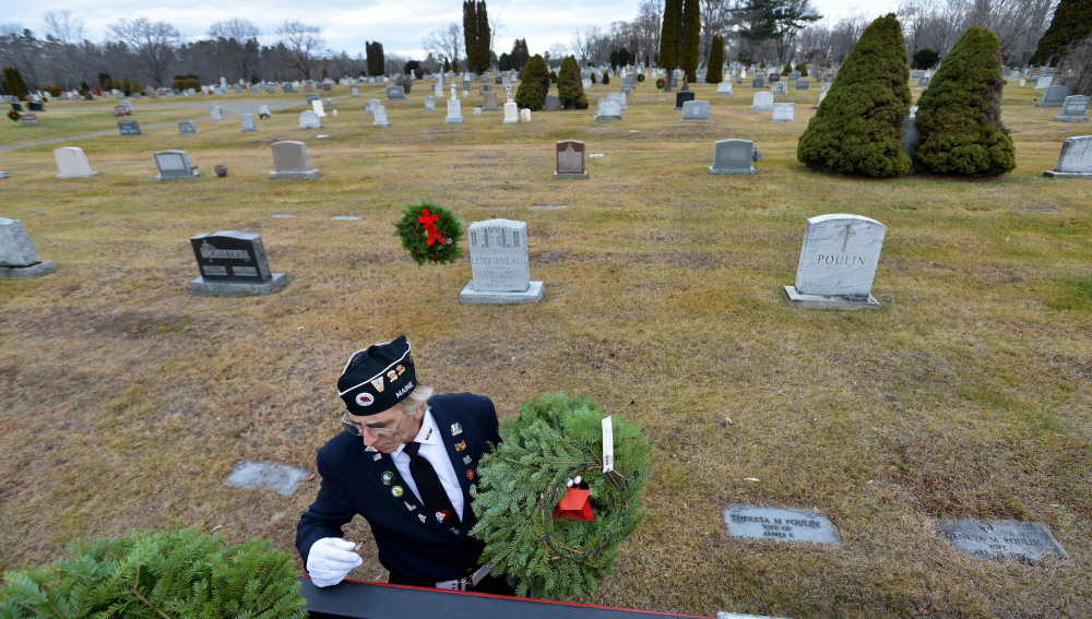 Paul Pontbriand, president of Waterville VFW Post 1285's men's auxiliary, grabs wreaths from a pickup truck to delivers them to veterans' graves Saturday at St. Francis Cemetery on Grove Street in Waterville.