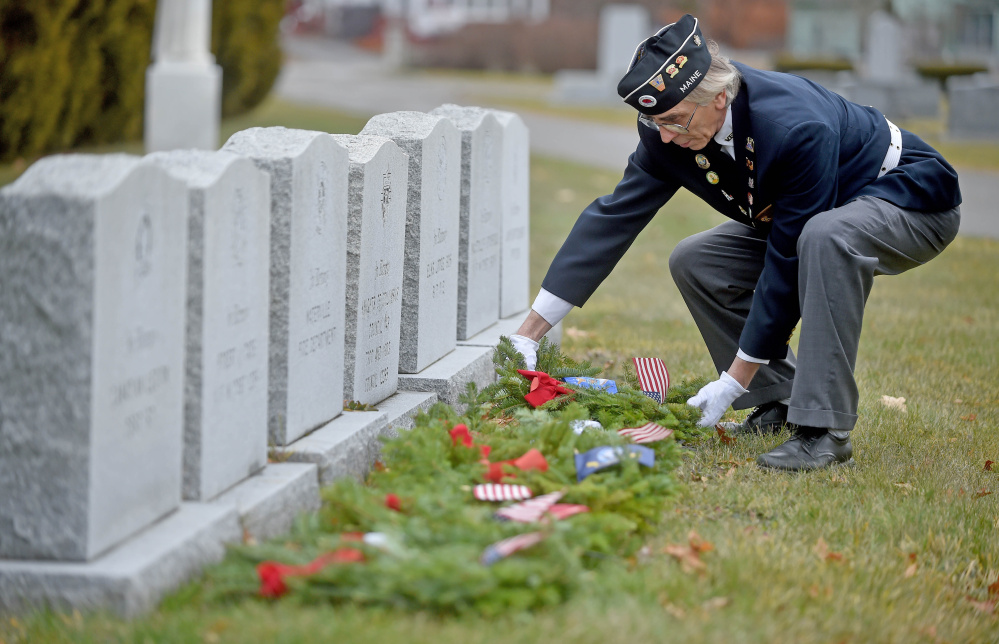 Paul Pontbriand, president of Waterville VFW Post 1285's men's auxiliary, places a wreath on a military veteran's grave Saturday at St. Francis Cemetery on Grove Street in Waterville.