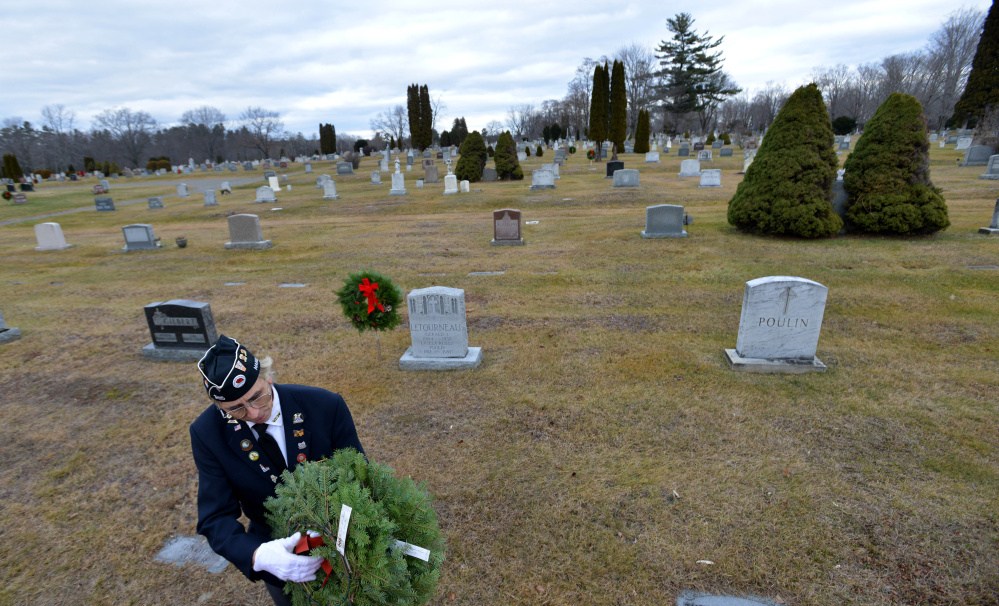 Paul Pontbriand, president of Waterville VFW Post 1285's men's auxiliary, holds a wreath destined for a veteran's grave Saturday at St. Francis Cemetery on Grove Street in Waterville.