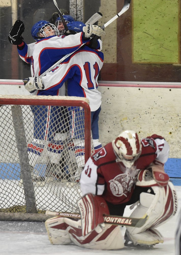 Messalonskee High School's Jared Cunningham, center back, is swarmed by teammates Dylan Brown, left back, and Dustin Brown, back right, as Bangor High School goalie Derek Fournier (31) takes a knee in the second period Saturday at Sukee Arena in Winslow.