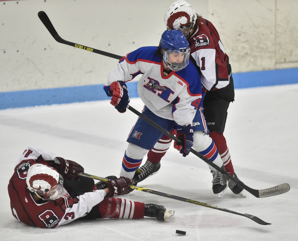 Messalonskee High School's Sam Bell, center, battles for the puck with Bangor High School's Cameron Burpee (13) left and Ben Lane (11), right, Saturday at Sukee Arena in Winslow.