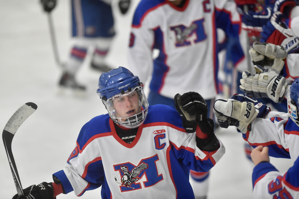 Messalonskee High School's Jared Cunningham (19), left, celebrates his second period goal with teammates Saturday at Sukee Arena in Winslow.