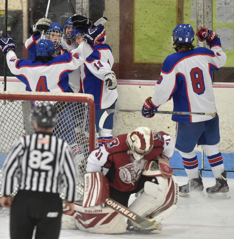 Messalonskee High School's Jared Cunningham, center back, is swarmed by teammates as Bangor High School goalie Derek Fournier (31) takes a knee in the second period Saturday at Sukee Arena in Winslow.