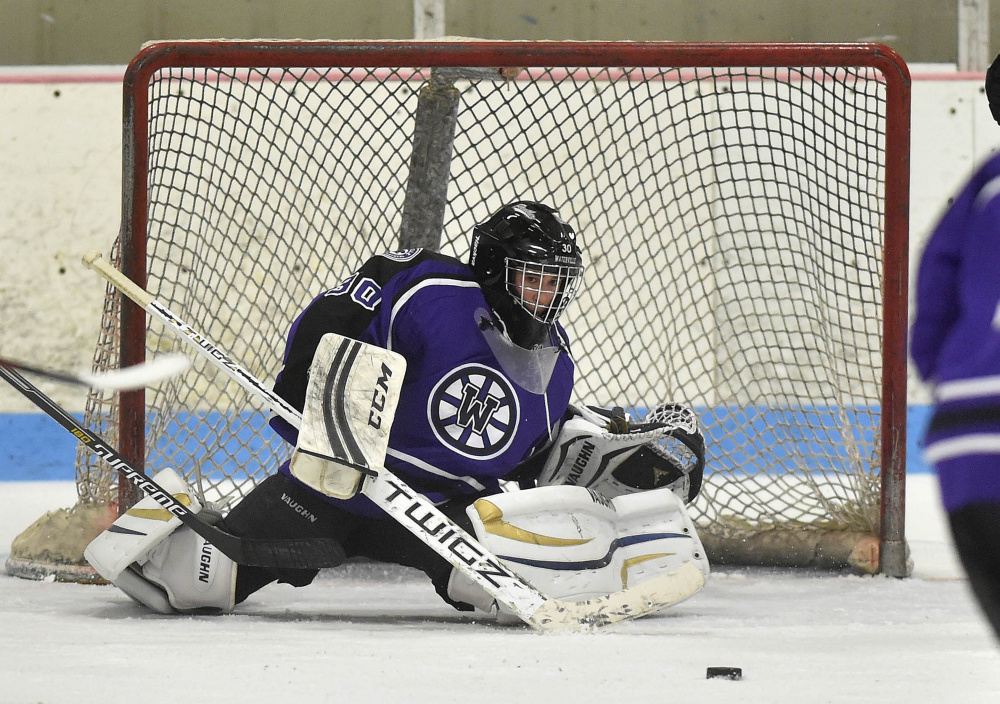 Waterville Senior High School goalie Nathan Pinette (30) makes a save against Winslow High School on Saturday at Sukee Arena in Winslow.