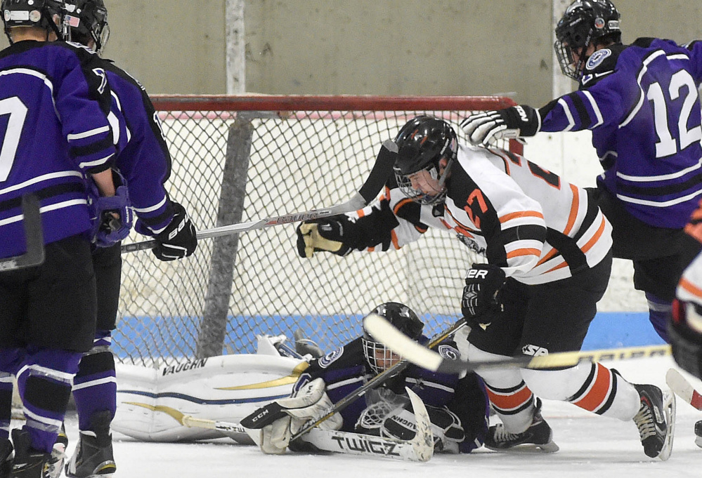Waterville Senior High School goalie Nathan Pinette (30) falls on the puck as Winslow High School's Nick West (27) tries to grab the rebound and Waterville's Zachary Smith (12) tries to defend Saturday at Sukee Arena in Winslow.