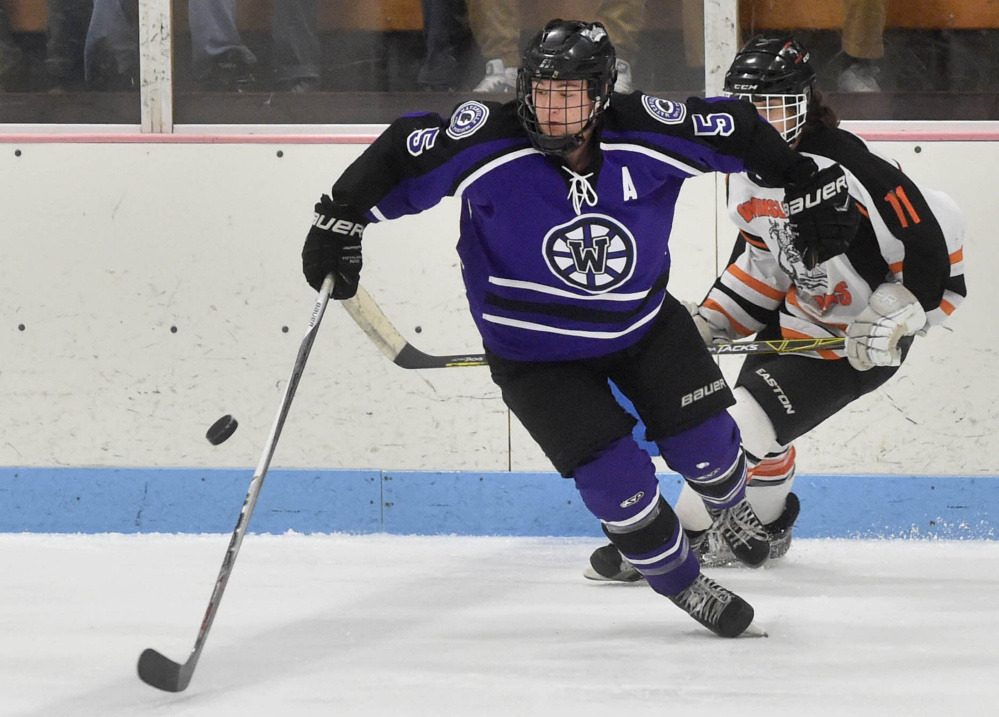 Waterville Senior High School's Andrew Rodrigue (5) skates away with the puck as Winslow High School's Logan Denis (11) pursues Saturday at Sukee Arena in Winslow.
