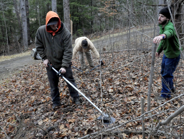 This year's lack of snow has given Waterville Parks and Recreation workers a chance to do some trail maintenance along walking and skiing paths at the Quarry Road Recreation Area. Working Monday are, from left, Kail Demerchant, Chris Lill and Jack Flynn. The area opened Thursday and has some man-made snow to keep skiers happy.