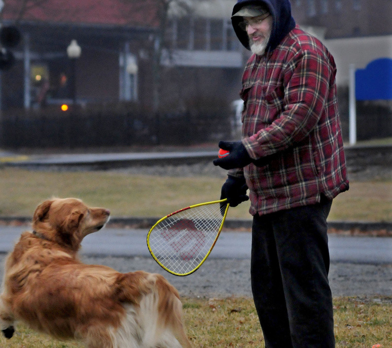 "Ray Cole gets ready to hit a ball with a racquet ball racket for his dog Bubba at Head of Falls in Waterville on Monday. ""This is a good stress reliever for me,"" Cole said as the two enjoyed the mild weather, which is expected to continue until the end of the month."