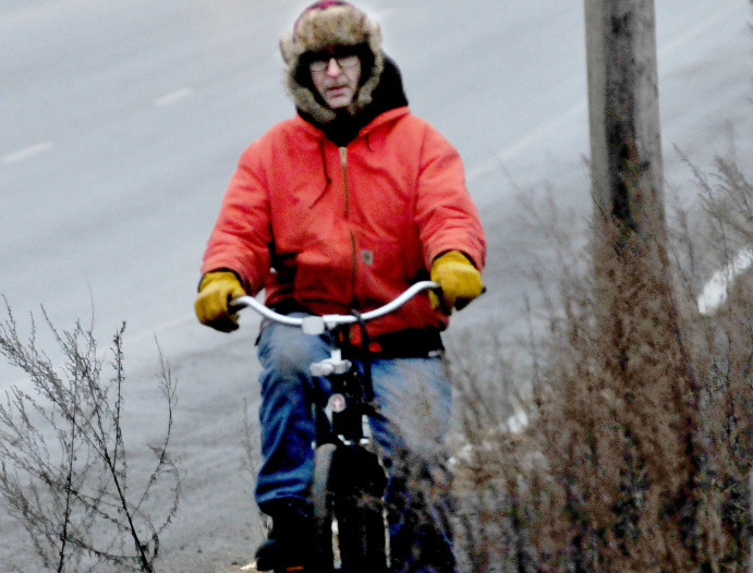 "Tim Jurdak rides his bike in Waterville during a misty day on Monday. Asked about the weather Jurdak said, ""I prefer snow over the freezing rain that is supposed to come later tonight."" The mild weather is expected to continue until at least the end of the month."
