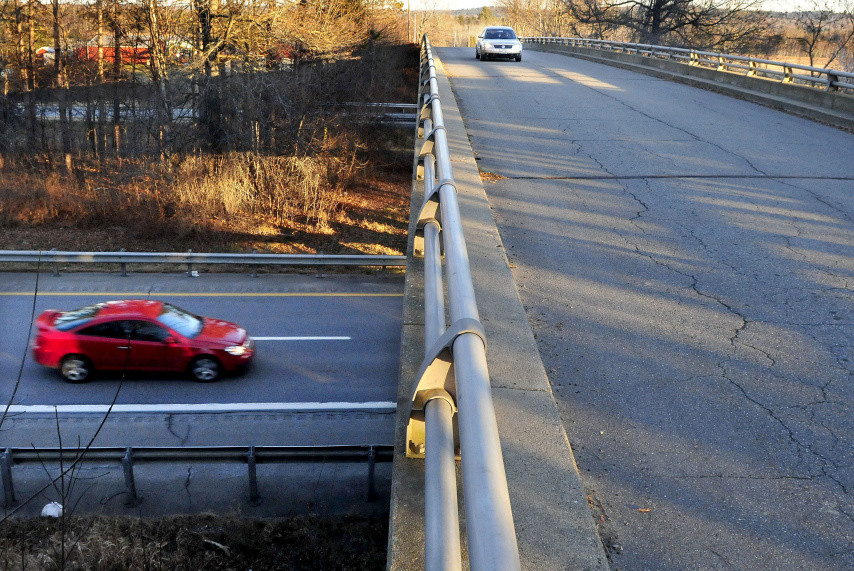 A vehicle travels west on the Trafton Road in Waterville as another passes under the overpass on Interstate 95 last month. A public meeting will be held on a proposed interchange at the site near the Sidney line.