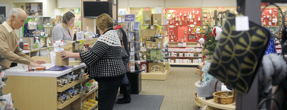Customers purchase gifts Monday at Stacy's Hallmark in Augusta. The Water Street business is closing at the end of the year and the building is being sold.
