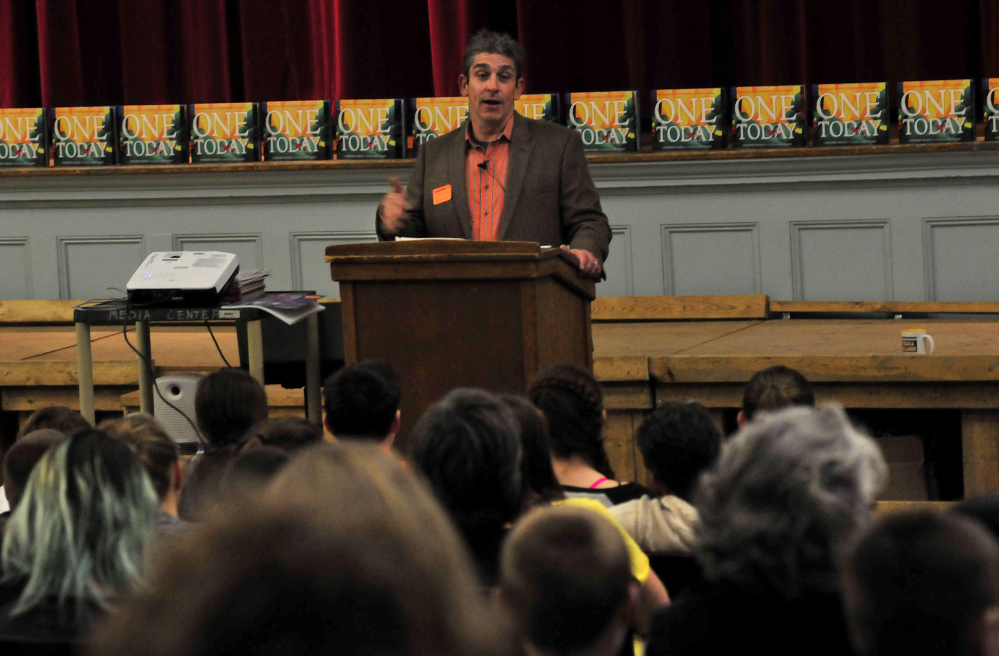 """Poet Richard Blanco reads one of his poems to students at Winslow Junior High School on Tuesday.  His book """"One Today"""" is behind him. Blanco was scheduled to read later Tuesda at Waterville's Opera House."""